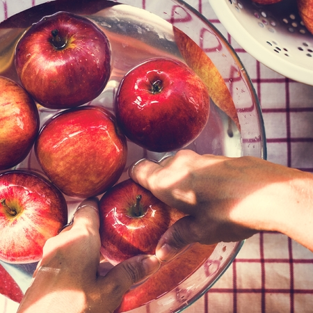Aerial view of hands washing apples in bowl