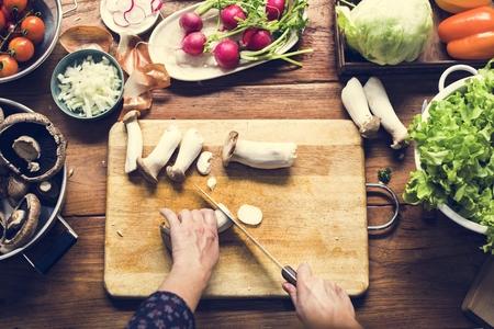 Aerial view of hand with knife cutting mushroom 版權商用圖片