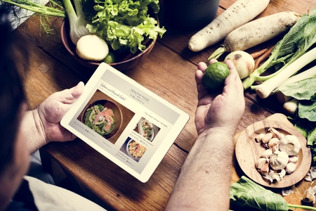 A man in a kitchen holding a fresh bergamot and reading a recipe of healthy food Stock Photo