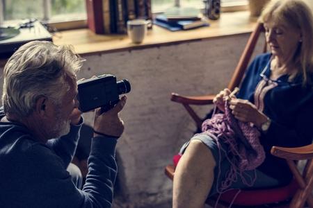 Senior man taking wife photo while knitting handicraft hobby Reklamní fotografie