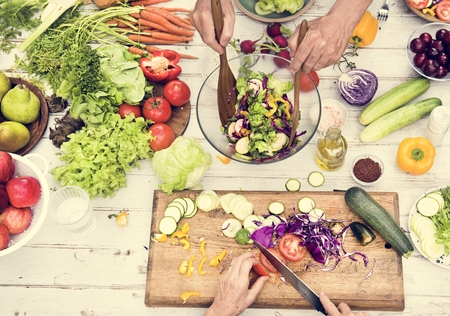 Aerial view of hands cutting various fresh vegetable