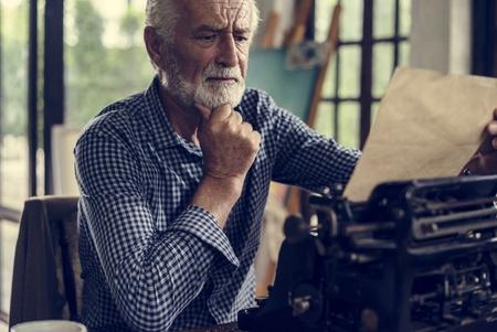 Senior man using typewriter Reklamní fotografie