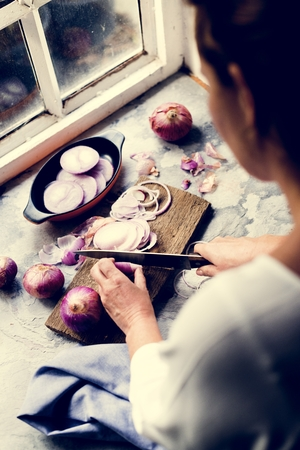 Closeup of hand with knife cutting slicing red onion 写真素材