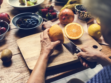 Closeup of hand with knife cutting orange 版權商用圖片