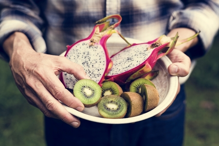 Closeup of hands holding bowl with cut dragon fruits and kiwi inside