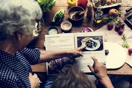 Hände zeigen auf Kochbuchrezept Standard-Bild
