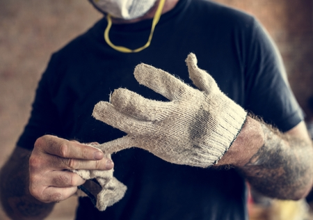 Handyman with tattoo pulling out a glove Foto de archivo