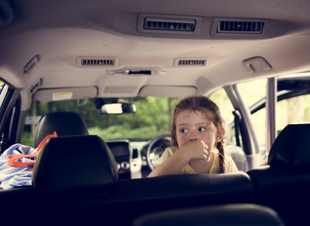 Closeup of young caucasian girl sitting thoughtful inside the car