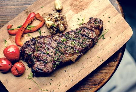Grilled steak on wooden plate