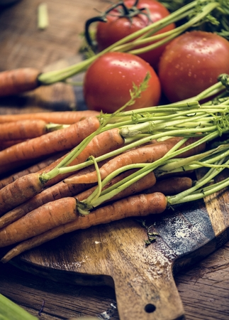 Closeup of fresh organic carrots and tomato on wooden table Imagens