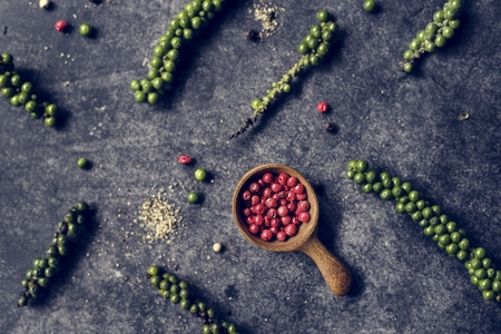 Aerial view of fresh peppercorns on black background