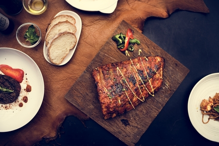 Closeup of pork ribs steak on wooden board food styling