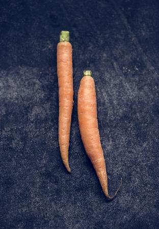 Closeup of yellow fresh organic carrots on black background