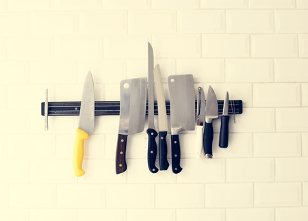 Set of knives hanging on the white wall Фото со стока