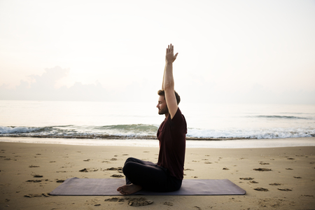 Man practicing yoga on the beach 版權商用圖片