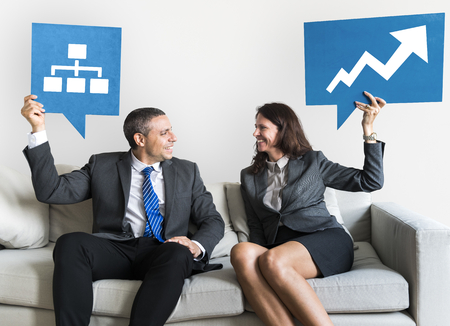 Business people holding speech bubbles with growth icons Foto de archivo