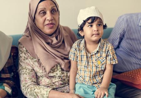 Muslim boy sitting with his grandmother