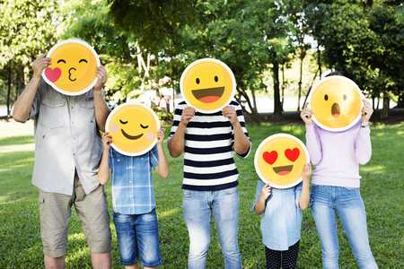 Happy family holding up emojis