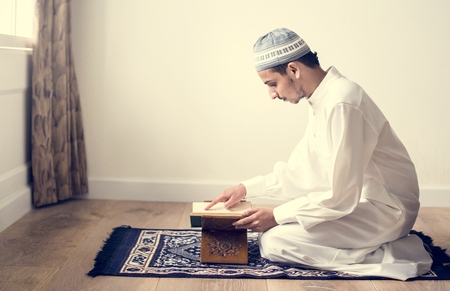 Muslim man studying The Quran Stock Photo - 104032452