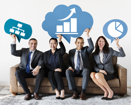 Diverse business people holding speech bubbles with development icons