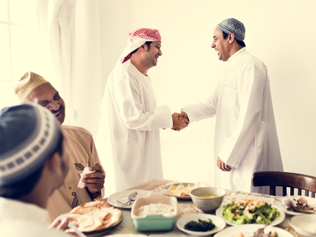 Muslim men shaking hands at lunchtime Stock Photo