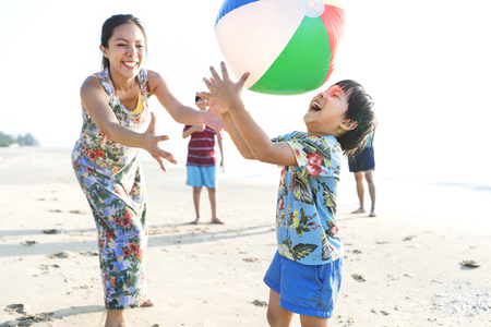 Asian family playing at the beach Imagens