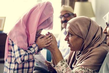 Muslim girl payng respect to mother