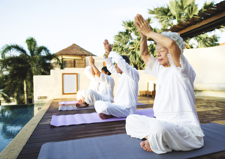 Group of seniors practicing yoga in the morning Banco de Imagens - 104034044