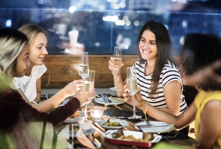 Girl friends having a dinner together at a rooftop bar Foto de archivo
