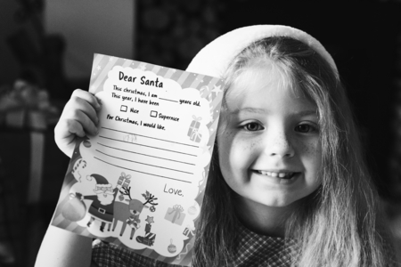 Little girl holding her Christmas wishlist