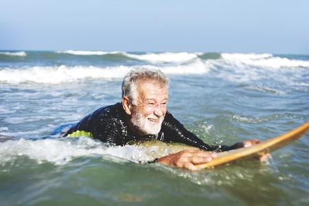 Een senior man op een surfplank Stockfoto