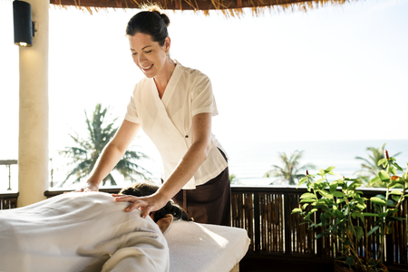 Female massage therapist giving a massage at a spa Stock Photo