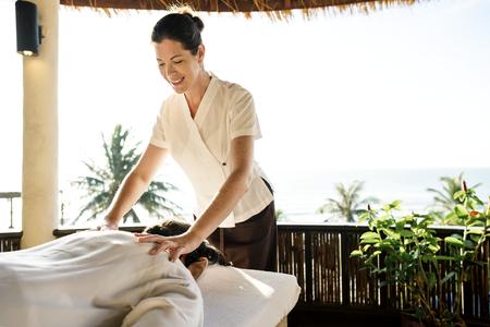 Female massage therapist giving a massage at a spa Archivio Fotografico