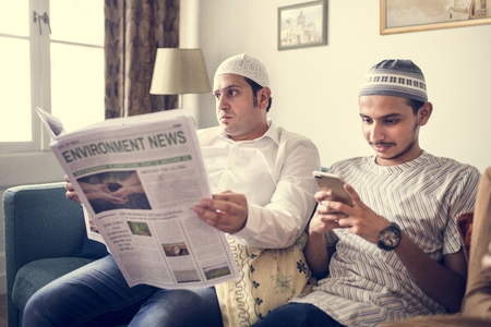 Muslim family reading the news
