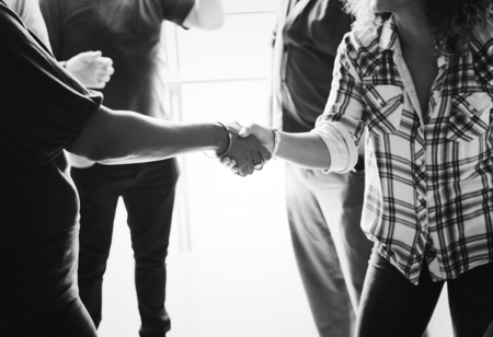 Diverse woman shaking hands together