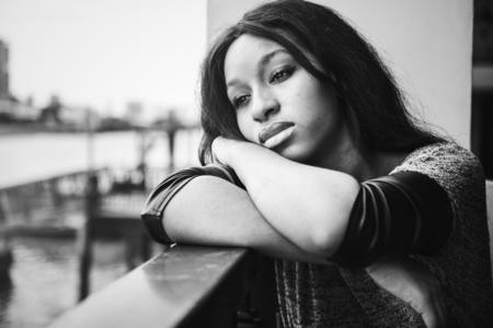 Afroamerikanerfrau sitzt und betrachtet etwas