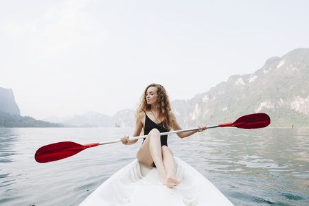 Woman paddling a canoe through a national park Imagens
