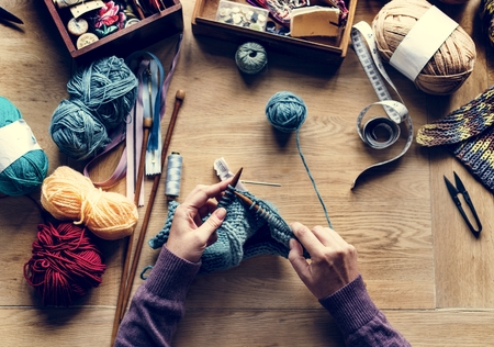 Aerial view of hands knitting on wooden table Standard-Bild - 104392045