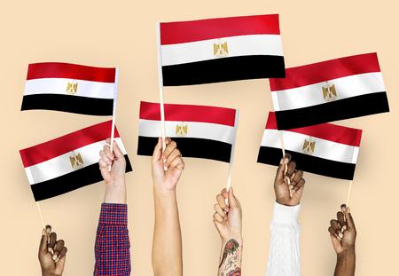 Hands raising Egypt national flags Stock Photo