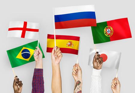 Hände, die Nationalflaggen von England, Spanien, Japan, Portugal, Russland und Brasilien hissen