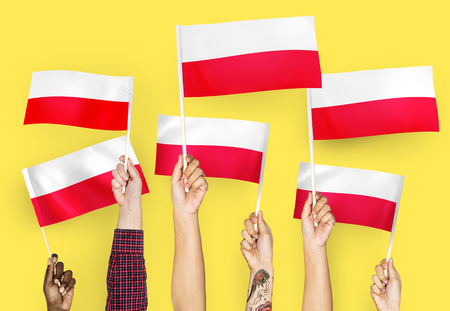 Hands waving the flags of Poland