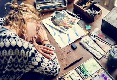 Closeup of artist woman taking a nap on work table Stock fotó