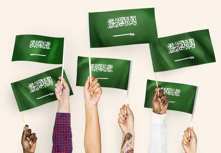 Manos agitando las banderas de Arabia Saudita