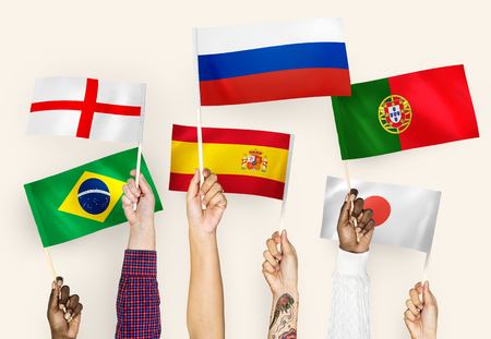 Hands waving the flags of England, Spain, Japan, Portugal, Russia, and Brazil Stock Photo