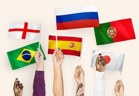 Mani che sventolano le bandiere di Inghilterra, Spagna, Giappone, Portogallo, Russia e Brasile