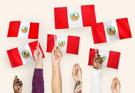 Hands waving the flags of Peru 版權商用圖片 - 104675211