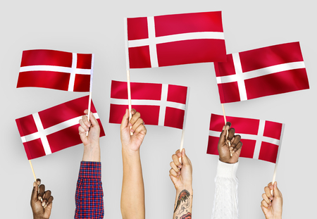 Hands waving the flags of Denmark 写真素材