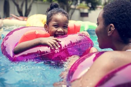 Primer plano de una madre negra y su hija disfrutando de la piscina con tubos inflables