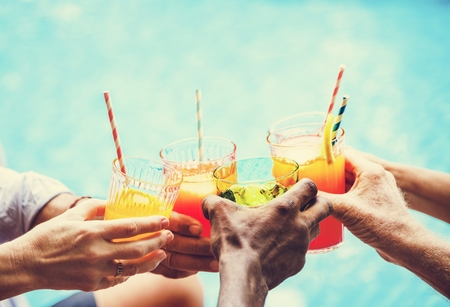 Closeup of diverse hands clinking drinks together