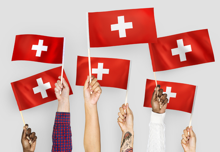 Hands waving the flags of Switzerland Banque d'images - 104675579